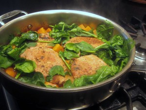 Pork in skillet with baby spinach
